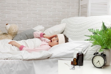 sick cold little child girl lies in bed with fever Stock Photo