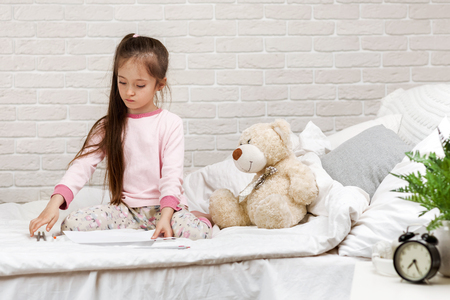 cute little girl drawing pictures while lying on bed. Kid painting at home 스톡 콘텐츠