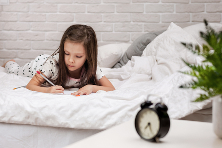 cute little girl drawing pictures while lying on bed. Kid painting at home Stock Photo - 123692246