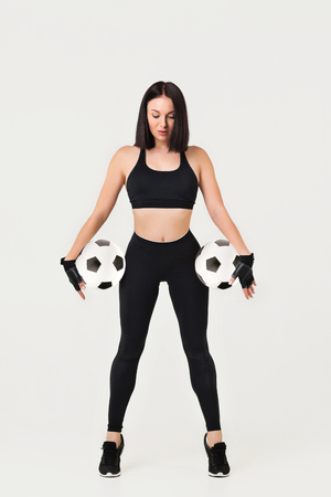 beautiful athletic woman with soccer ball posing isolated on gray background 写真素材