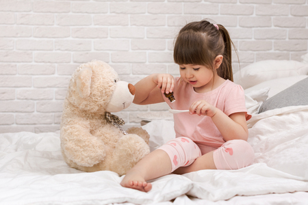cute child girl playing doctor with teddy bear at home. Stock Photo - 123692250