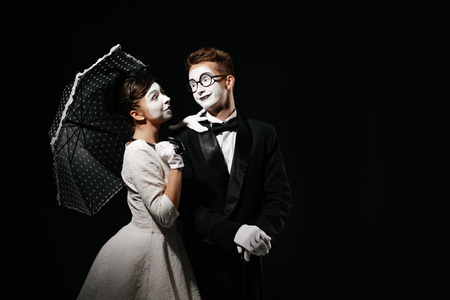 portrait of couple mime with umbrella on black background. man in tuxedo and glasses and woman in white dress. space for text