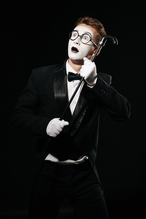surprised mime man in tuxedo and glasses posing with walking stick on black background
