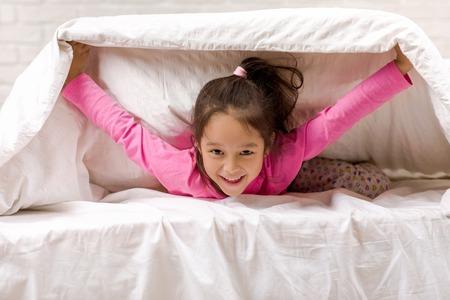 feliz mañana bebé en la cama. niño se mete en la cama
