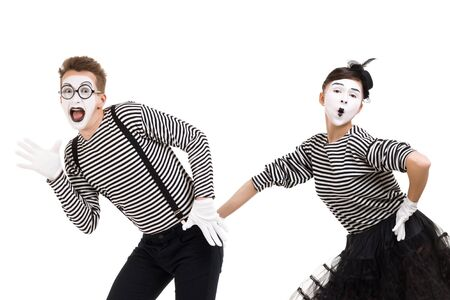 mimes in striped shirts. Man and woman dressed as actors of pantomime theater dancing isolated on white background