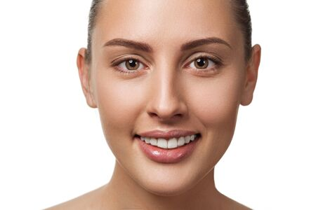 Piękno zbliżenie portret kobiecej twarzy z naturalnej skóry patrząc na kamery i uśmiechnięty. model z jasnym makijażem na białym tle