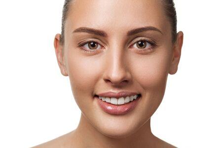 Schönheitsnahaufnahmeporträt des weiblichen Gesichts mit natürlicher Haut, die Kamera betrachtet und lächelt. Modell mit hellem Make-up auf weißem Hintergrund