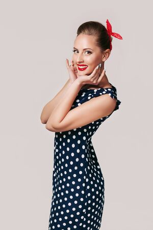 portrait of smiling pin up woman in polka dot dress. cute girl in retro style