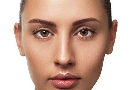 Schönheit schließen herauf Porträt des weiblichen Gesichts mit natürlicher Haut, die Kamera betrachtet Modell mit hellem Make-up auf weißem Hintergrund