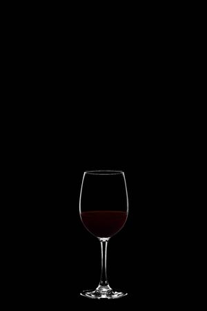 Wineglass with red wine isolated on black background