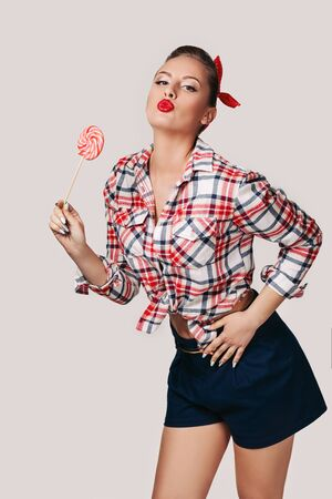 beautiful pin-up woman with pink lollipop on gray background Imagens