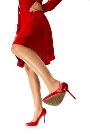 woman is kicking. girl in red dress kicks with her leg in high shoes to camera on white background Imagens