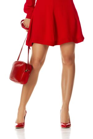 Woman in red dress standing with red purse bag and high heels shoes isolated on white background.