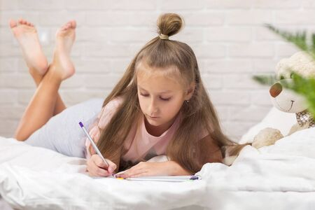 cute little girl drawing pictures while lying on bed. Kid painting at home. happy morning