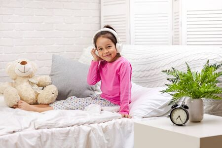 little child baby girl listening to the music with the headphones. happy morning