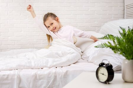 cute little child girl wakes up from sleep in bed in the morning