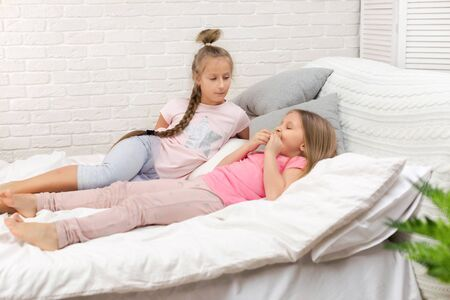 two cute children girls playing in the bedroom. pajama party and friendship. Stock Photo