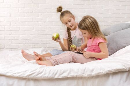 two cute children girls use digital tablet in bed. child playing on tablet pc.