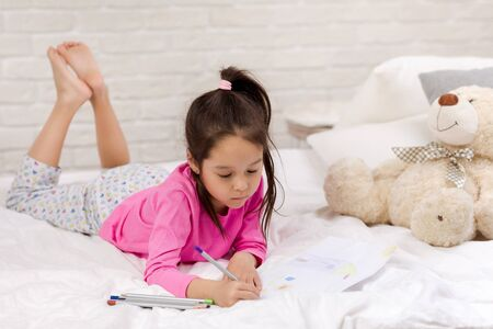 cute little girl drawing pictures while lying on bed. Kid painting at home Stock Photo
