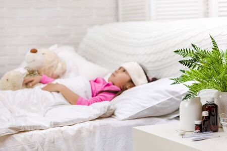 Sick little child girl lying in bed. Cold flu season. focus on medication and pill bottle Stock Photo