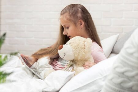 cute little child girl with teddy bear lies in bed uses digital tablet. child playing on tablet pc.