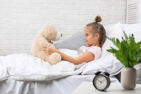 adorable little child girl playing with teddy bear in bed in morning
