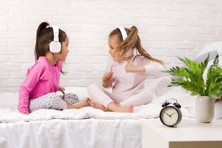 little children girls listening to the music with the headphones and dancing on bed. pajama party and friendship.