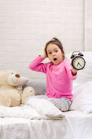 Surprised cute little child girl in pyjamas with clock in bed. good morning