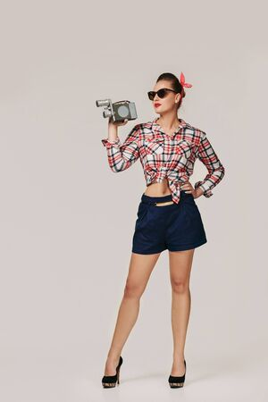 pin-up girl in plaid shirt and sunglasses holding old vintage camera. Stock Photo