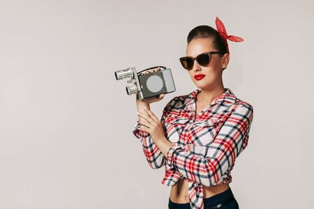 pin-up girl in plaid shirt and sunglasses holding old vintage camera. copy space for text