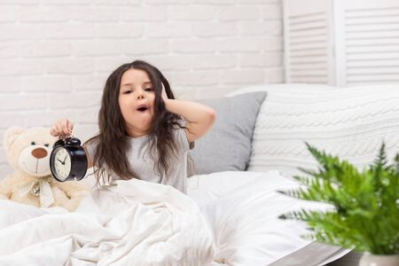 cute surprised little child girl in pyjamas with clock in bed. good morning Stock Photo