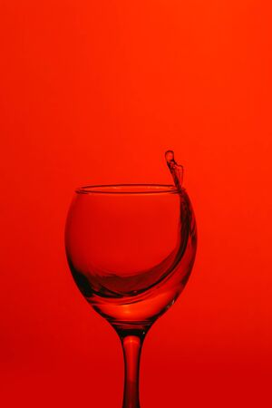 splash of water in wineglass isolated on red background. Stock Photo
