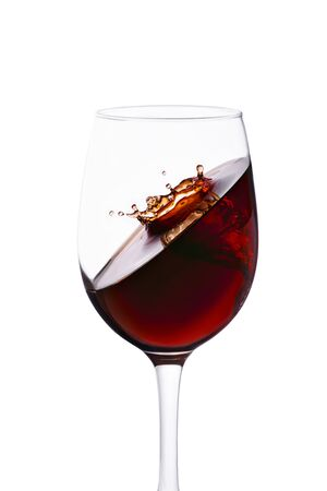 splash with crown of red wine in glass isolated on white background.
