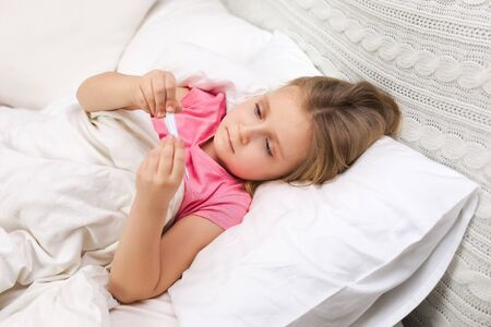 Sick little child girl lying in bed with thermometer. Cold flu season