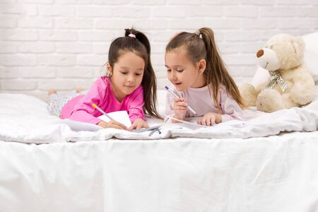 kids drawing pictures while lying on bed. pajama party and friendship. Stock Photo