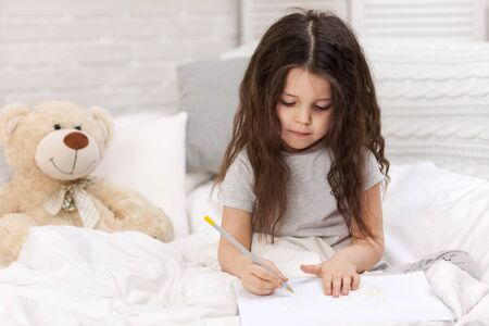 cute little girl with teddy bear drawing pictures while lying on bed. Kid painting at home Stock Photo
