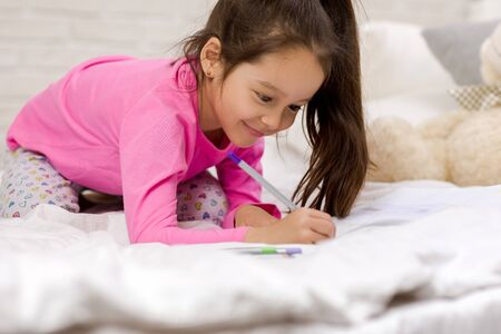 funny little girl drawing pictures while lying on bed. Kid painting at home Stock Photo