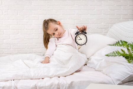 cute little child girl in pyjamas with clock in bed. good morning Stock Photo