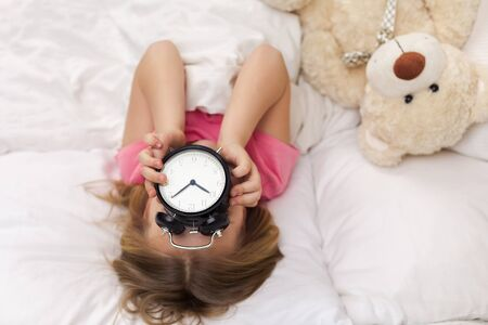 cute little child girl in pyjamas with clock in bed. good morning. top view Stock Photo