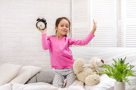 happy little child girl in pyjamas with clock in bed. good morning
