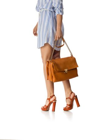 Brown womens shoes and leather bag. Beautiful female legs wearing summer high heeled sandals in blue dress and brown woman handbag on white background.
