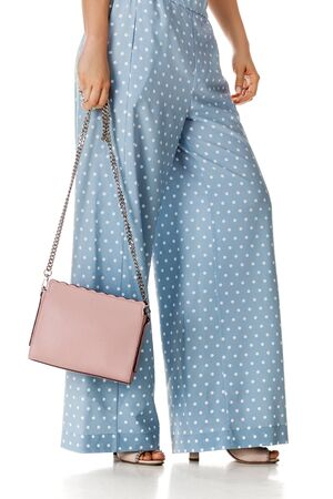 woman wearing summer high heeled sandals in polka-dot blue pants and pink woman handbag on white background.
