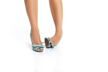 Twist ankle. Woman in blue high heels shoes on white background. ankle sprain. 스톡 콘텐츠