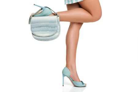 blue womens shoes. Woman in high heels shoes with blue handbag on white background. Stock Photo