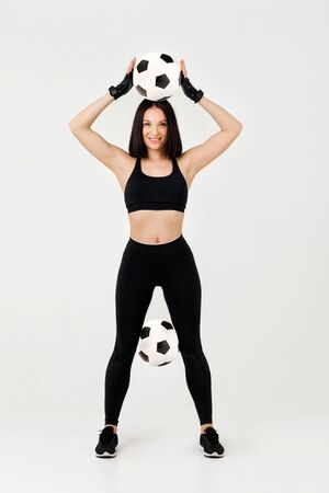 beautiful athletic woman with soccer ball posing isolated on gray background Stock Photo