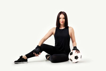 beautiful athletic woman with soccer ball sitting on floor isolated on white background