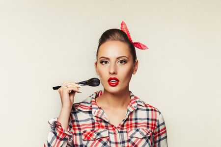 surprised pin-up girl in plaid shirt holding make-up brush. retro style woman applying blusher. copy space for text Stock Photo - 128613188