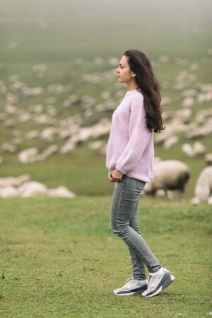 Happy young woman in a sweater against herds of sheep in the mountains