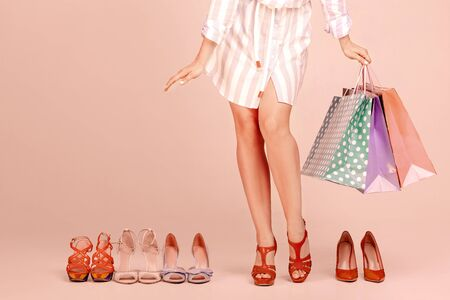 young woman with shopping bags stands between new pairs of shoes Stock Photo - 128613201