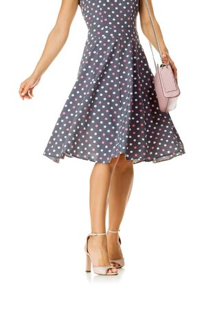 pink womens shoes and leather bag. Beautiful female legs wearing summer high heeled sandals in polka-dot dress and pink woman handbag on white background. Stock Photo